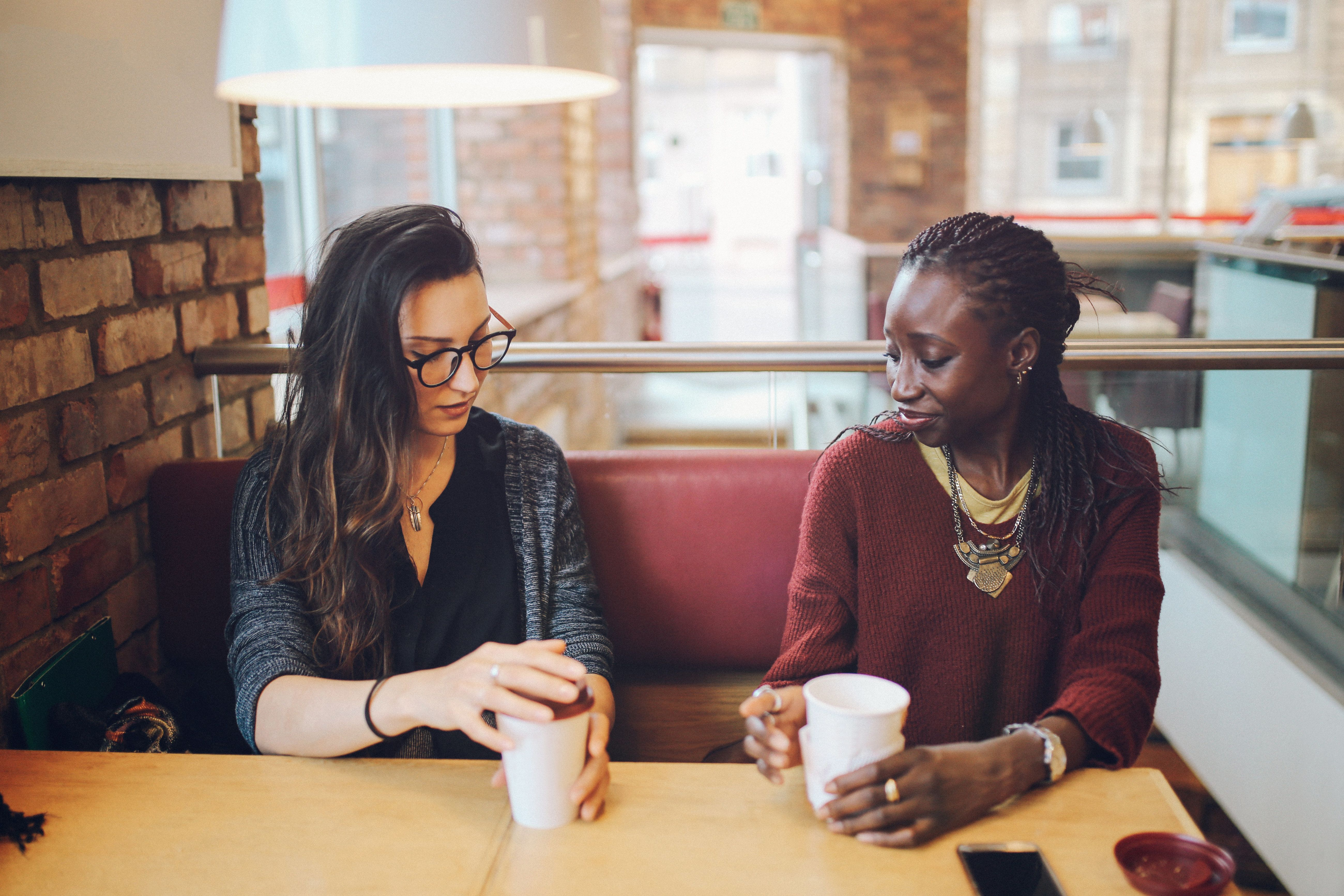 Portrait of a two young women of different ethnicities, sitting together outdoors, at the coffee break, chatting.