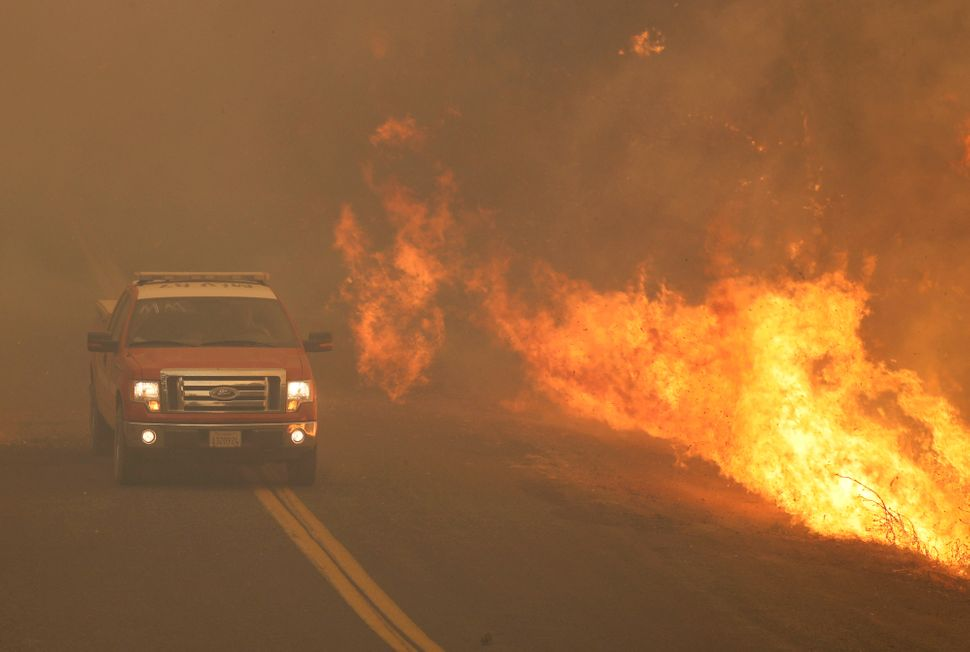 A fire truck rushes past flames that overran a road at the River Fire in Lakeport, California on Tuesday.