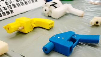 Seized plastic handguns which were created using 3D printing technology are displayed at Kanagawa police station in Yokohama, south of Tokyo, in this photo taken by Kyodo May 8, 2014. Yoshimoto Imura became the first man to be arrested in Japan for illegal possession of two guns he created himself using 3D printing technology, Japanese media said on Thursday. The 27-year-old, a college employee in the city of Kawasaki, was arrested after police found video online posted by Imura claiming to have produced his own guns. Gun possession is strictly regulated in Japan. Police raided Imura's home and found five guns, two of which could fire real bullets, Japanese media said. Mandatory credit REUTERS/Kyodo (JAPAN - Tags: CRIME LAW SCIENCE TECHNOLOGY TPX IMAGES OF THE DAY) ATTENTION EDITORS - THIS IMAGE HAS BEEN SUPPLIED BY A THIRD PARTY. FOR EDITORIAL USE ONLY. NOT FOR SALE FOR MARKETING OR ADVERTISING CAMPAIGNS. MANDATORY CREDIT. JAPAN OUT. NO COMMERCIAL OR EDITORIAL SALES IN JAPAN. THIS PICTURE IS DISTRIBUTED EXACTLY AS RECEIVED BY REUTERS, AS A SERVICE TO CLIENTS