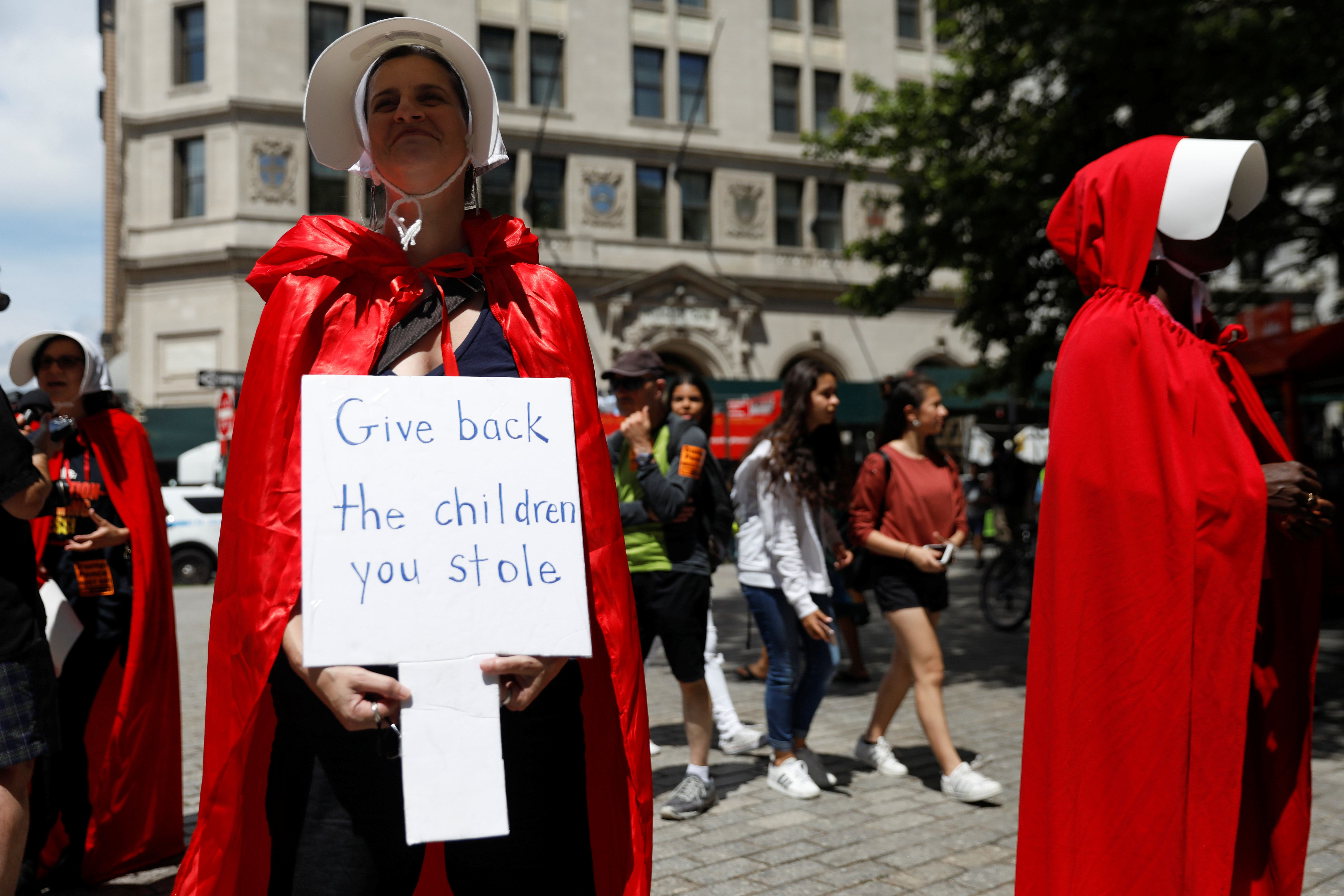 """Women dressed in red gowns as worn in the """"Handmaids Tale"""" protest U.S. Vice President Mike Pence and Department of Homeland Security (DHS) Secretary Kirstjen Nielsen outside the DHS Cybersecurity Summit in Manhattan, New York, U.S., July 31, 2018.  REUTERS/Shannon Stapleton"""