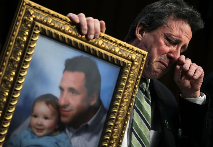 Neil Heslin, father of 6-year-old Sandy Hook victim Jesse Lewis, holds a picture of him with Jesse as he testifies during a h