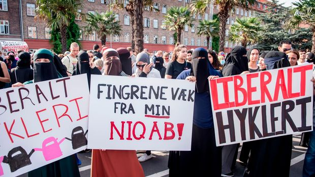 Women wearing niqab to veil their faces take part in a demonstration on August 1, 2018, the first day of the implementation of the Danish face veil ban, in Copenhagen, Denmark. - Denmark's controversial ban on the Islamic full-face veil in public spaces came into force as women protested the new measure which fines anyone wearing the garment. Human rights campaigners have slammed the ban as a violation of women's rights, while supporters argue it enables better integration of Muslim immigrants into Danish society. (Photo by Mads Claus Rasmussen / Ritzau Scanpix / AFP) / Denmark OUT        (Photo credit should read MADS CLAUS RASMUSSEN/AFP/Getty Images)