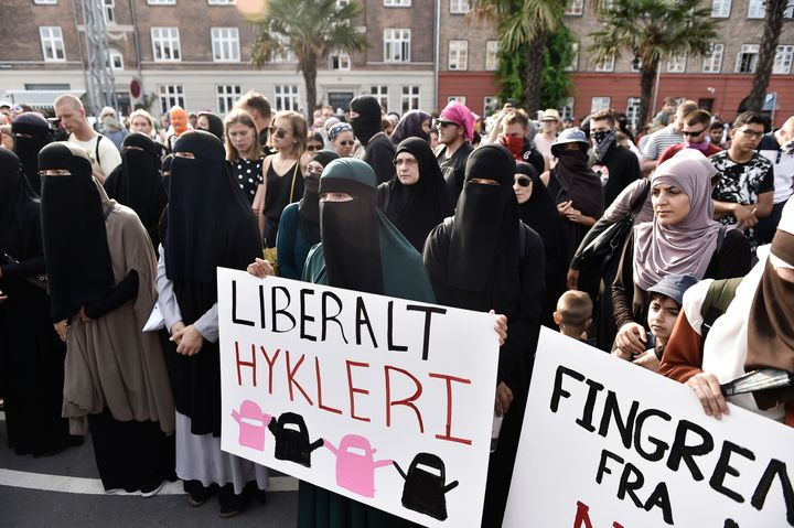 Women carry signs defending their right to wear Islamic face veils during a protest in Copenhagen on Aug. 1, 2018.