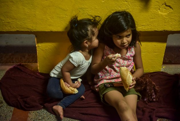 Sisters Ashly, 3, and Sol, 8, both from Honduras, eat donated sandwiches as their family camps next to...