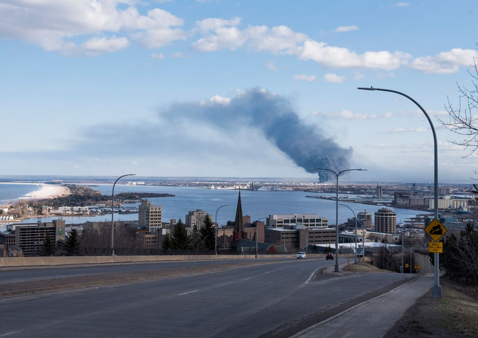 A fire at the Husky Oil Refinery in Superior, Wisconsin, is seen in the distance on April 26. Mitchell toured the site o