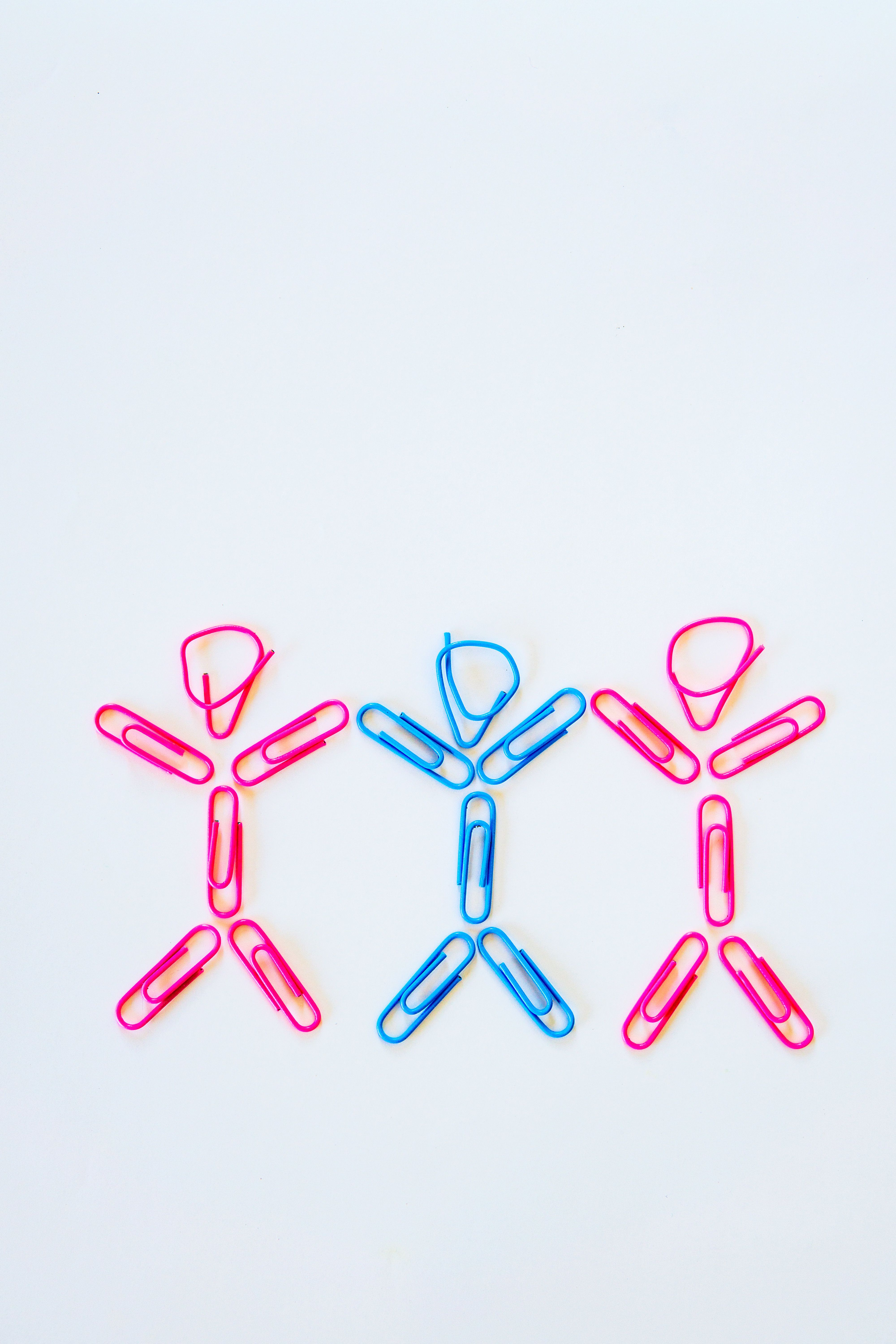 A conceptual idea of a polygamous bisexual relationship.  Two women and one man holding hands, with arms raised.  Represented by stereotypical pink colours for girls and blue for boys, it also represents alternative lifestyles, LGBTQ issues and simplicity.  Studio shot on a white background.
