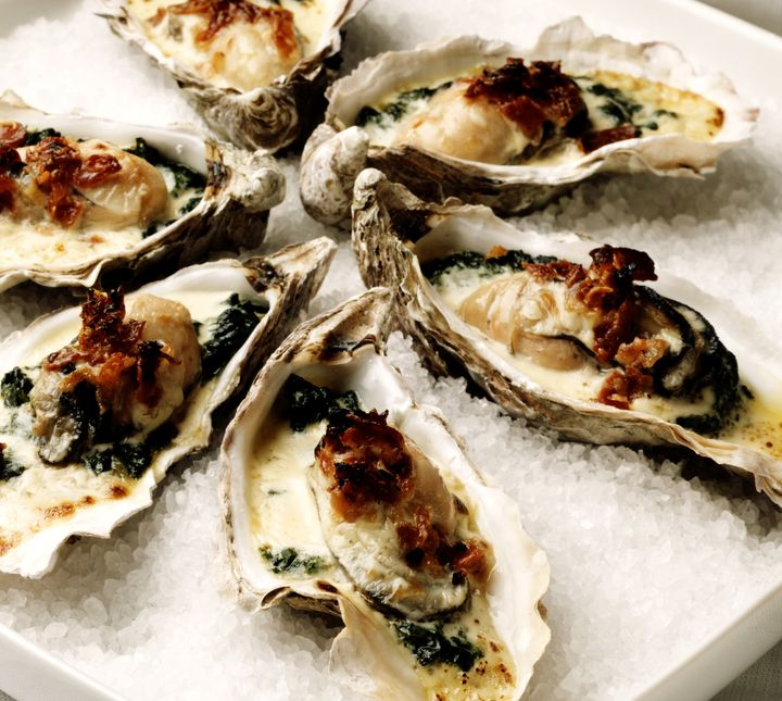 Oysters Rockefeller are baked or broiled with a rich sauce of butter, herbs and breadcrumbs.