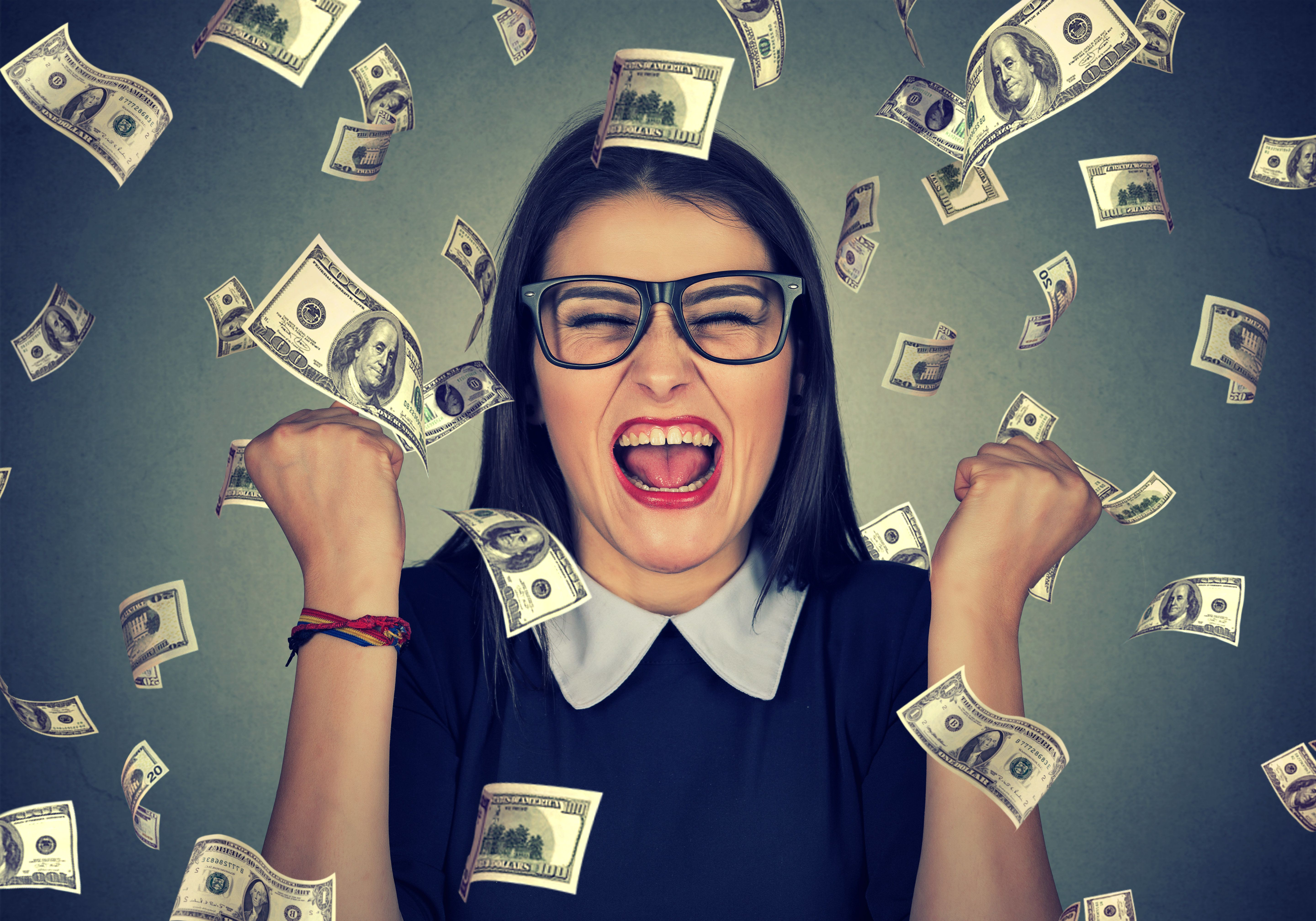 Portrait happy woman exults pumping fists ecstatic celebrates success under money rain falling down dollar bills banknotes isolated on gray wall background. Financial achievement  concept