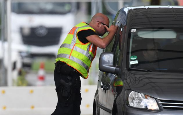 Ein Polizist kontrolliert am 22. Juli ein Fahrzeug an der bayerisch-österreichischen Grenze bei