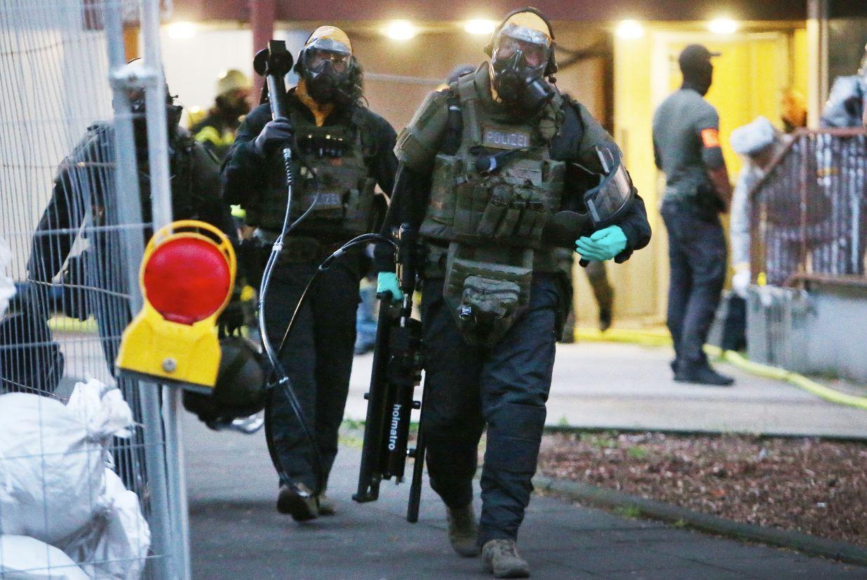 SEK-Beamte mit Schutzmasken verlassen ein Hochhaus in Köln. Die Kleidung soll sie vor Rizin