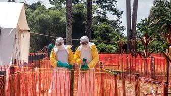 Health workers operate within an Ebola safety zone in the Health Center in Iyonda, near Mbandaka, on June 1, 2018. - The UN health agency and DRC authorities are rushing to contain the outbreak that has sickened 54 people in recent weeks, including 25 who have died. (Photo by Junior D. KANNAH / AFP)        (Photo credit should read JUNIOR D. KANNAH/AFP/Getty Images)