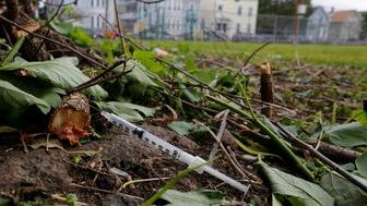 A used needle sits on the ground in a park in Lawrence, Massachusetts, U.S., May 30, 2017, where individuals were arrested earlier in the day during raids to break up heroin and fentanyl drug rings in the region, according to law enforcement officials.   REUTERS/Brian Snyder