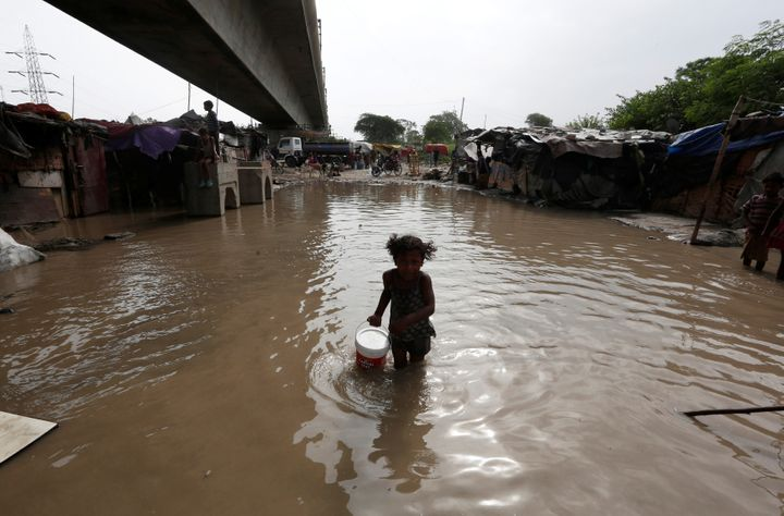 A girl carries drinking water as she wades through a flooded street after a rise in the waters of the Yamuna River in New Del