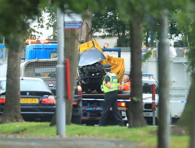 A car covered by a tarpaulin is removed from the scene on Bingley Road at the junction with Toller Lane in Bradford following a road traffic collision where four males died in a car which was being followed by an unmarked police vehicle when it crashed.