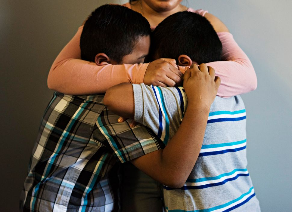 Jorge and Luis get a hug from their aunt Maylin, 20, who came to the United States with them.