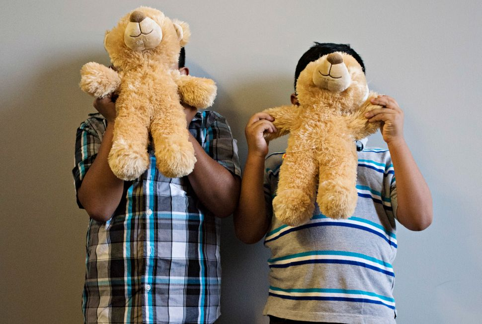Luis and Jorge hold up teddy bears in front of their faces.