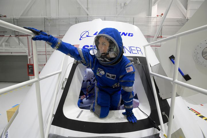 Boeing propulsion engineer Monica Hopkins climbs out of a mockup of the Starliner crew module, while wearing the craft's newl