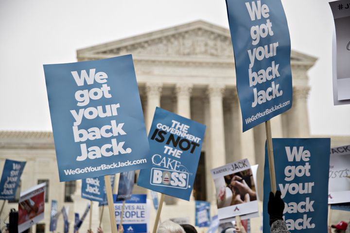 Demonstrators hold signs in support of Masterpiece Cakeshop owner Jack Phillips outside the U.S. Supreme Court on Tuesday, De