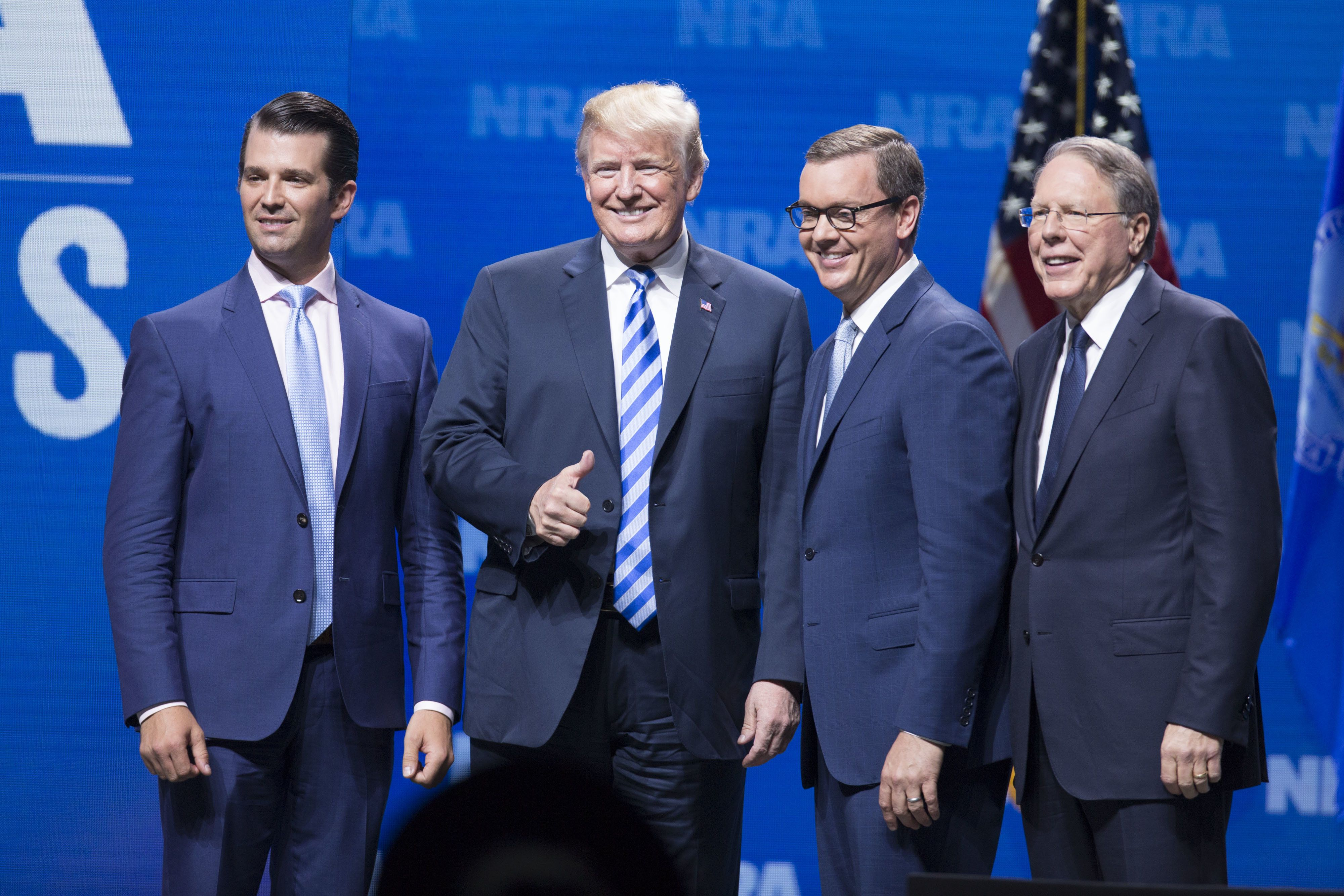 Donald Trump Jr., executive vice president of development and acquisitions with the Trump Organization Inc., from left, U.S. President Donald Trump, Chris Cox, chief lobbyist of the National Rifle Association (NRA), and Wayne LaPierre, chief executive officer of the NRA, stand for a photograph at the National Rifle Association Institute for Legislative Action (NRA-ILA) Leadership Forum during the NRA annual meeting in Dallas, Texas, U.S., on Friday, May 4, 2018. PresidentDonald Trumpdelivered a strong sign of support for the National Rifle Association at its annual meeting on Friday, as gun-rights advocates regroup in the wake of the mass shooting at a Florida high school. Photographer: Daniel Acker/Bloomberg via Getty Images