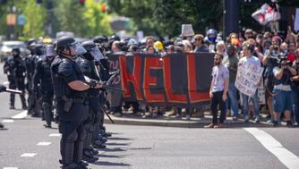 PORTLAND, OR - AUGUST 4: Members of the Portland Police stand guard on the SW Corner of Naito Parkway and SW Salmon, separating both sides at the Patriot Prayer Rally in downtown Portland, OR, on August 4, 2018. (Photo by Diego Diaz/Icon Sportswire via Getty Images).