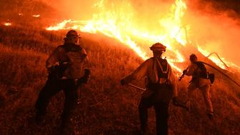 Firefighters conduct a controlled burn to defend houses against flames from the Ranch fire, as it continues to spreads towards the town of Upper Lake, California on August 2, 2018. - Thousands of firefighters in California made some progress against several large-scale blazes that have turned around 200,000 acres (80,940 hectares) into an ashen wasteland, destroyed expensive homes, and killed eight fire personnel and civilians in the most populous US state. (Photo by Mark RALSTON / AFP)        (Photo credit should read MARK RALSTON/AFP/Getty Images)