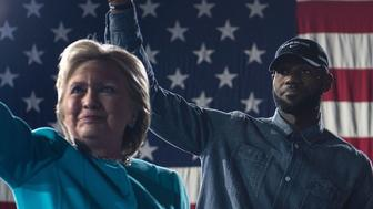 NBA basketball player Lebron James and Democratic presidential nominee Hillary Clinton arrive for a rally at the Cleveland Public Auditorium November 6, 2016 in Cleveland, Ohio. Donald Trump barnstorms five states Sunday while Hillary Clinton implores her most fervent supporters to get to the polls, in a frenetic final 48-hour dash to the US presidential election. / AFP / Brendan Smialowski        (Photo credit should read BRENDAN SMIALOWSKI/AFP/Getty Images)