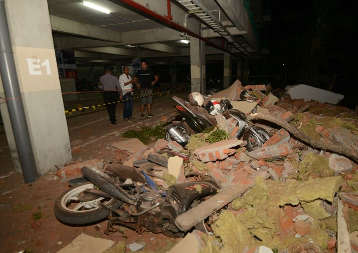 Residents look at bikes and debris at a mall in Bali's capital Denpasar on August 5, 2018 after a major earthquake rocked nei