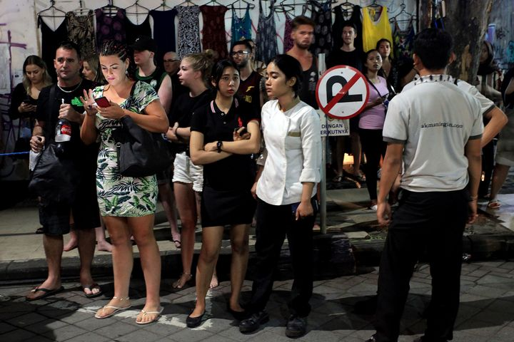 Foreign tourists and hotel staff stand on the street afer being evacuated in Bali's capital Denpasar on August 5, 2018, after