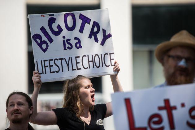 Una mujer alza una pancarta que dice: 'La intolerancia es un estilo de vida que se