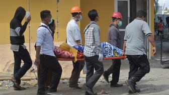 An injured quake victim is stretchered to a makeshift ward set up outside the Moh. Ruslan hospital in Mataram on the Indonesian island of Lombok on August 6, 2018, the morning after a 6.9 magnitude stuck the island. - Indonesian security forces and emergency workers raced on August 6 to rescue survivors of the powerful earthquake on Lombok that killed at least 82 people, as strong aftershocks sparked terror on the holiday island that suffered another deadly quake just a week ago. (Photo by ADEK BERRY / AFP)        (Photo credit should read ADEK BERRY/AFP/Getty Images)