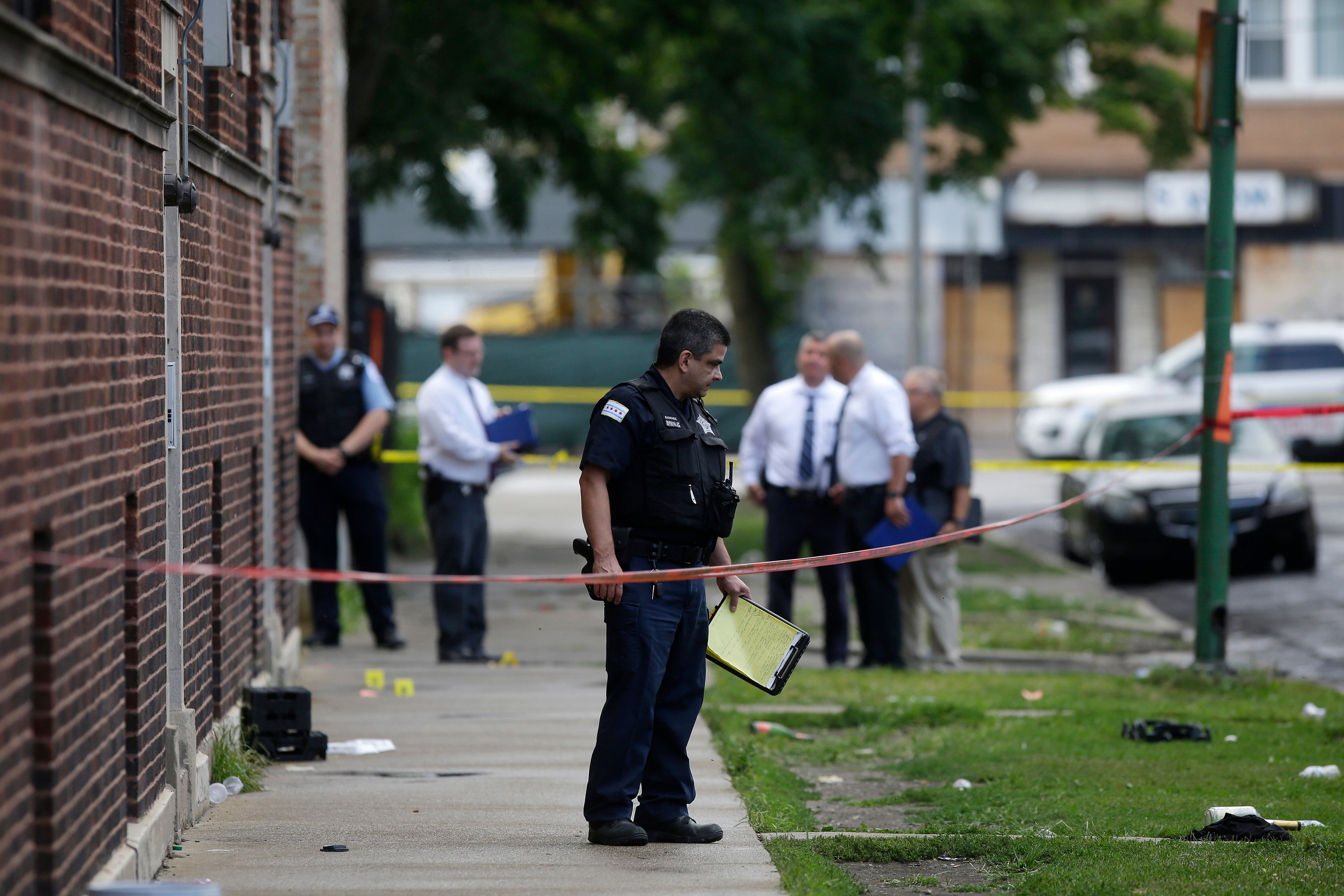 Chicago police officers and detectives investigate a shooting where multiple people were shot on Sunday.