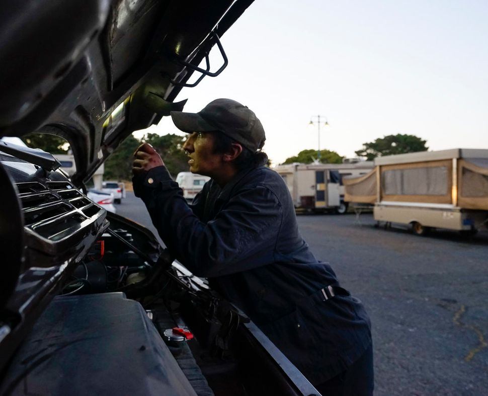 Amber Whitson works on the van she uses to pull her Fleetwood Pace Arrow recreational vehicle.