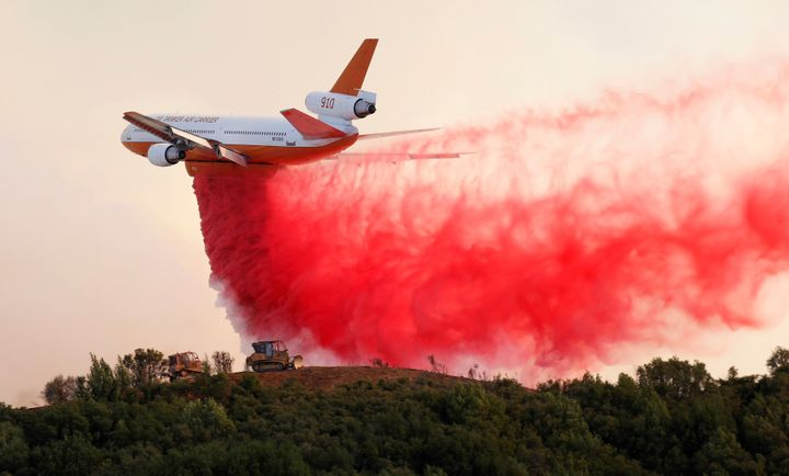 A DC-10 air tanker drops fire retardant along the crest of a hill to protect the two bulldozers below that were cutting fire