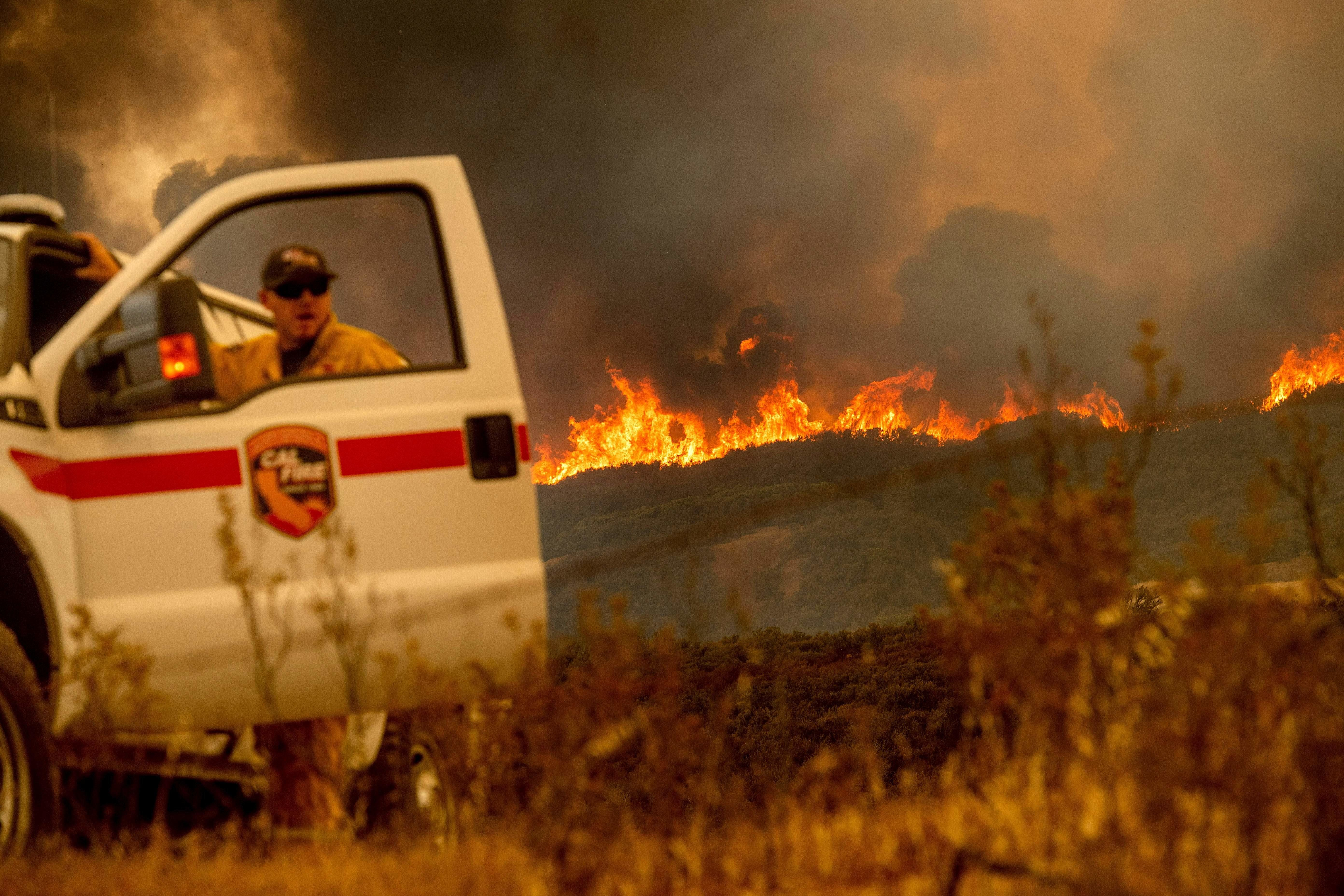 The Ranch fire, part of the Mendocino Complex fire, crests a ridge as Battalion Chief Matt Sully directs firefighting operati