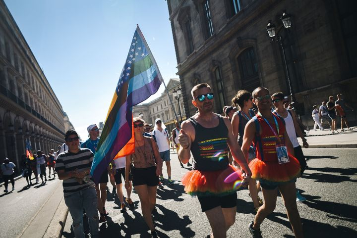 A man waves the rainbow flag as he takes part with others participants in the Rainbow Run, from Paris City Hall to Place de l