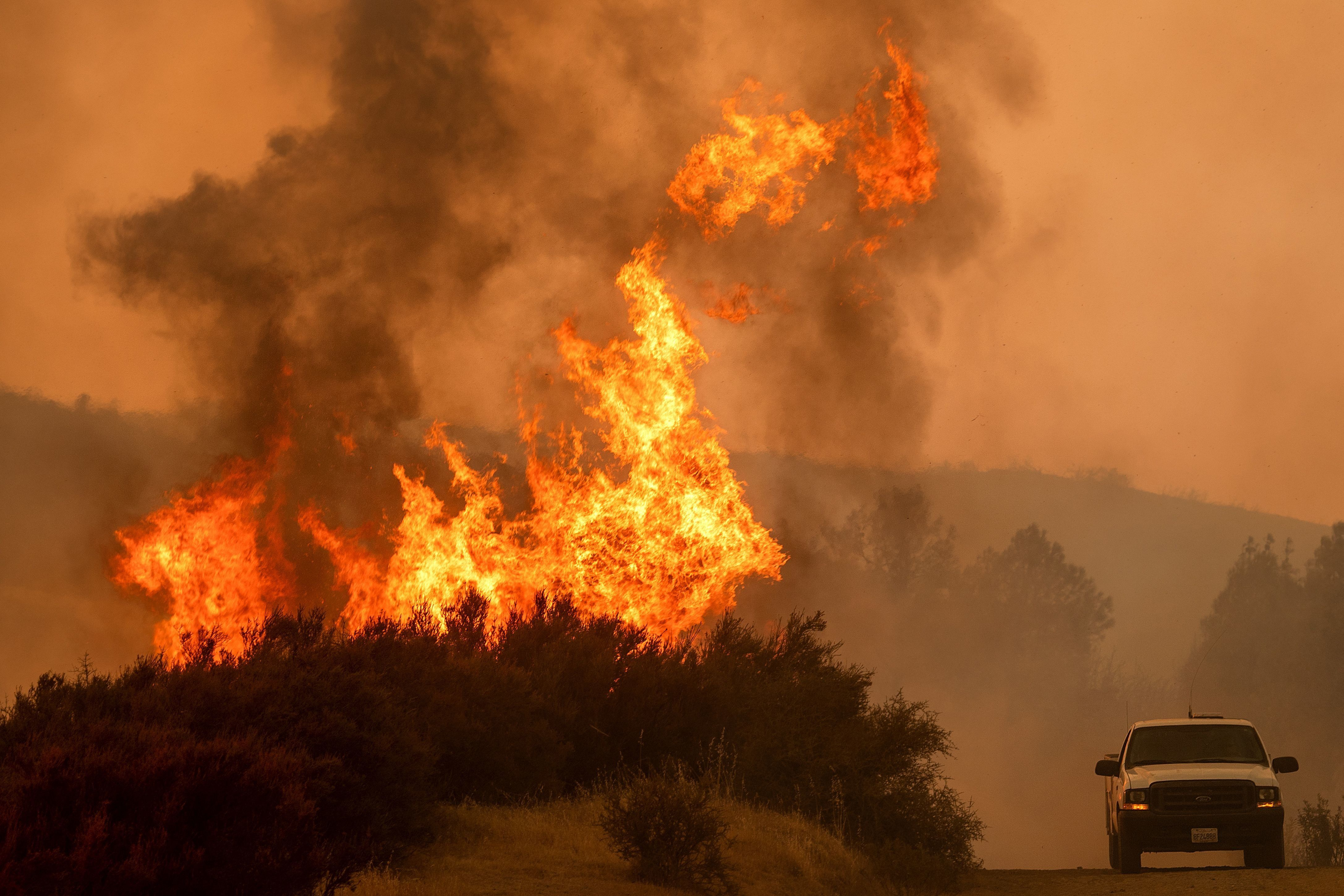 TOPSHOT - Flames leap above a vehicle on High Valley Rd as the Ranch Fire, part of the Mendocino Complex Fire, burns near Clearlake Oaks, California, on August 5, 2018. - Several thousand people have been evacuated as various fires swept across the state, although some have been given permission in recent days to return to their homes. (Photo by NOAH BERGER / AFP)        (Photo credit should read NOAH BERGER/AFP/Getty Images)