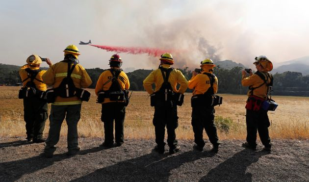 Firefighters watch as an air tanker drops fire retardant along the crest of a hill near Lakeport, California,...