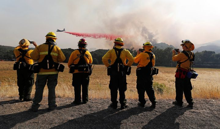 Firefighters watch as an air tanker drops fire retardant along the crest of a hill near Lakeport, California, on Aug. 2, 2018.