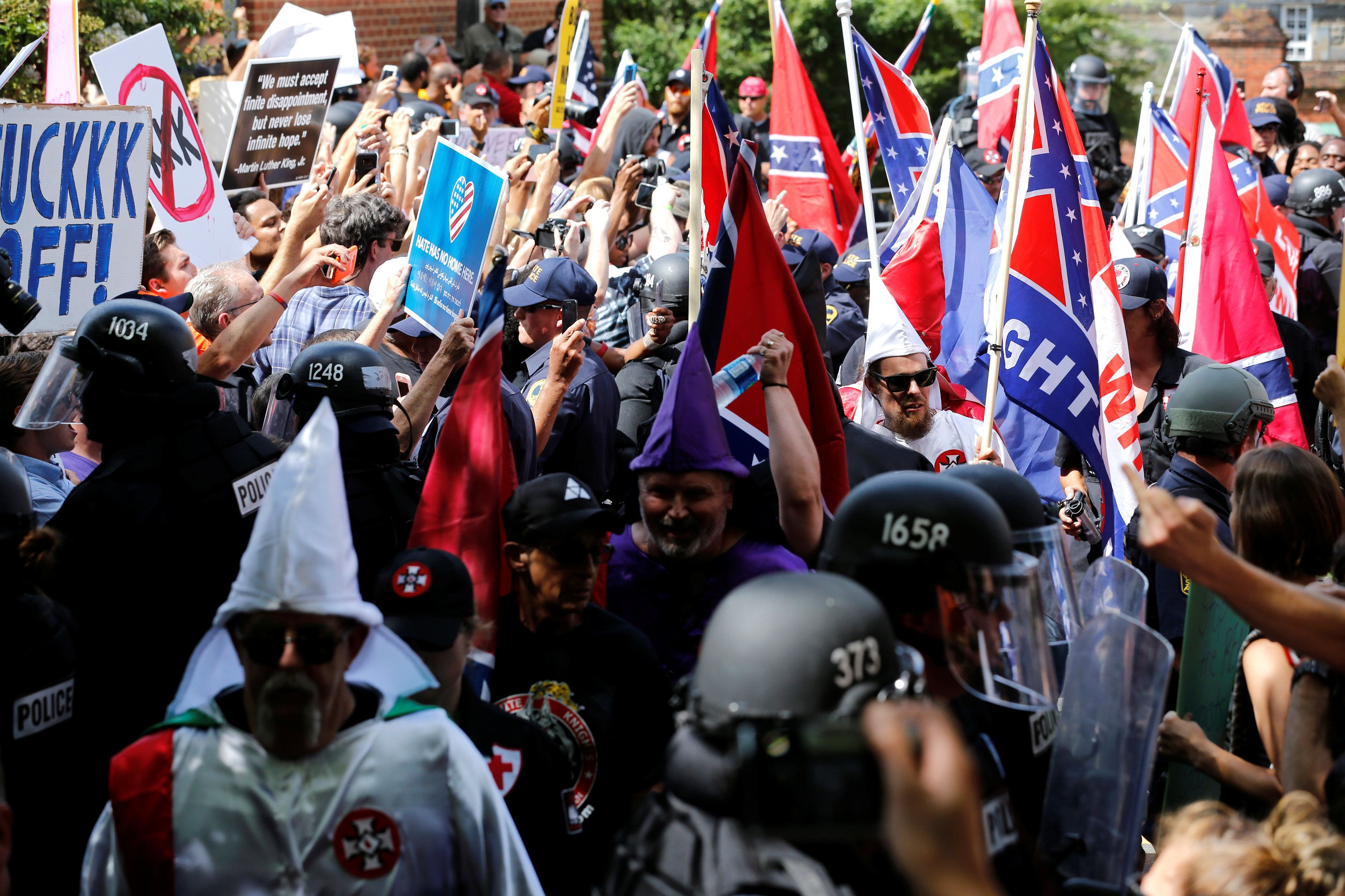 Riot police protect members of the Ku Klux Klan from counter-protesters as they arrive to rally in support of Confederate mon
