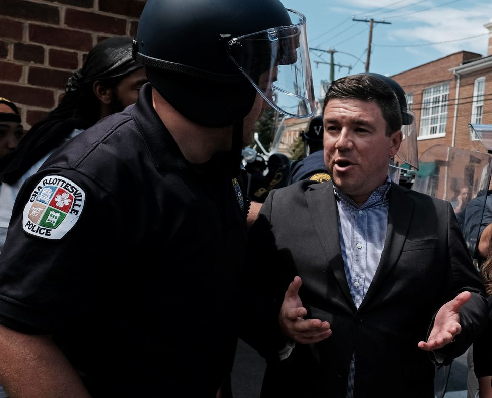 Unite The Right rally organizer Jason Kessler is escorted by police after he attempted to speak at a press conference in fron