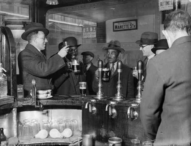The original photograph of customers raising a glass inside the Pillars of Hercules pub in Soho in November