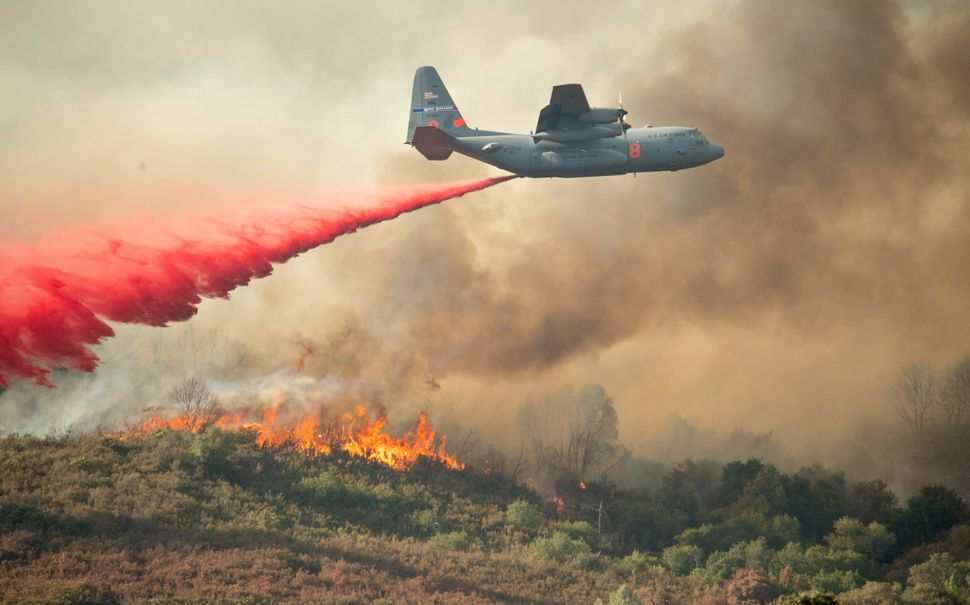 A U.S. Air Force plane drops fire retardant on a burning hillside in the Ranch Fire in Clearlake Oaks, California on Sunday,