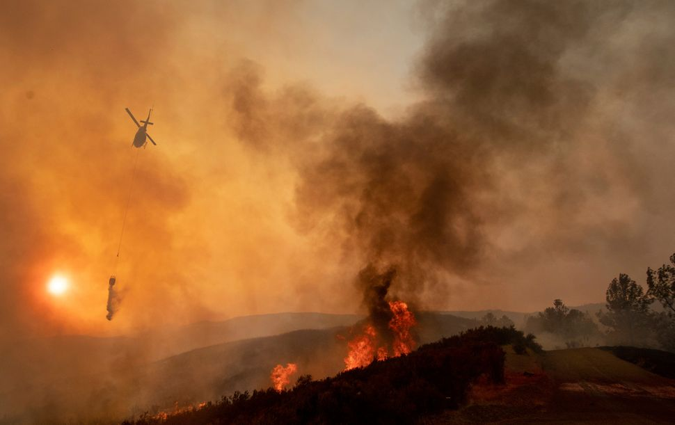 A helicopter drops water on a burning hillside during the Ranch Fire in Clearlake Oaks, California.