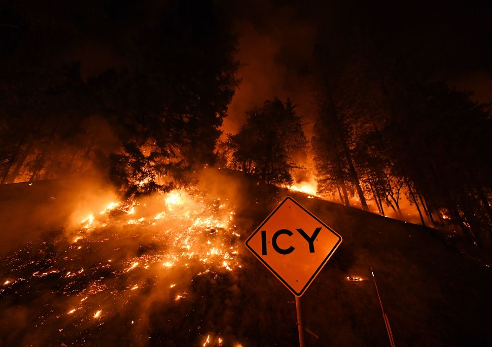A road sign warns for ice as the Carr Fire continues to spread toward the towns of Douglas City and Lewiston near Redding, Ca