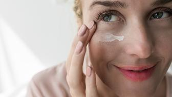 Pretty Caucasian woman applying skin care creme under eye.