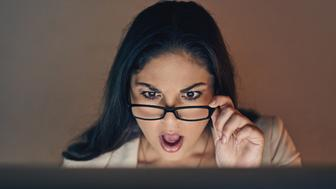 Shot of a young businesswoman using a computer and looking shocked during a late night at work