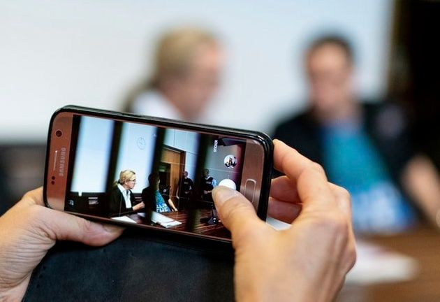 A woman takes a photo of a man in the dock of the court in
