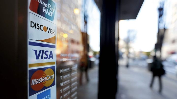 <p>Credit card logos are posted to the door of a business in Atlanta. U.S. household debt reached $13.2 trillion in the first quarter of this year, the 15th consecutive quarter increase.</p>
