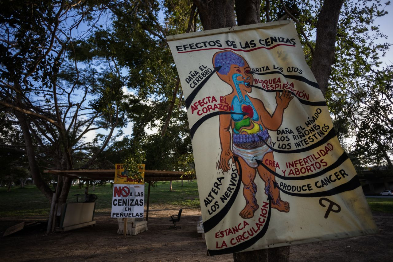 The sun sets on a protest camp in Peñuelas. A hand painted sign describes the effects that coal ash in the air and water can have on physical health.