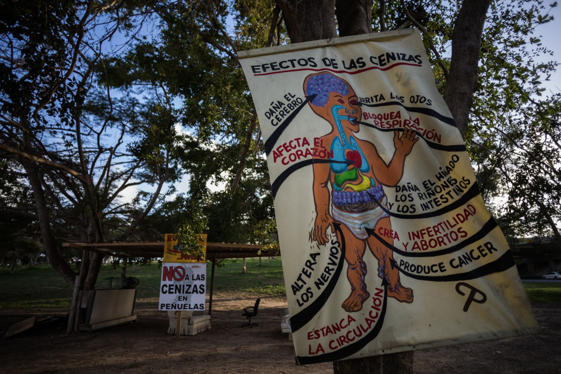 The sun sets on a protest camp in Peñuelas. A hand painted sign describes the effects that coal ash in the air and wat